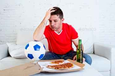 young soccer supporter man with ball and beer bottle watching football game on television sitting at home couch looking dejected sad and disappointed for failure or defeat wearing team jersey